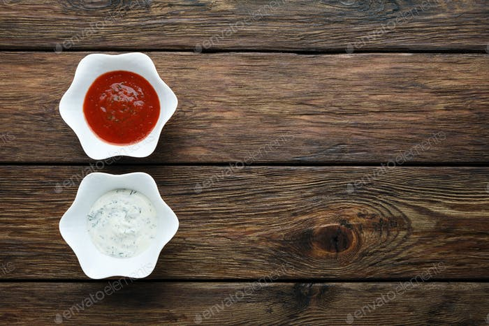 Ketchup mit Mayonnaise-Saucen auf Holz, Draufsicht.