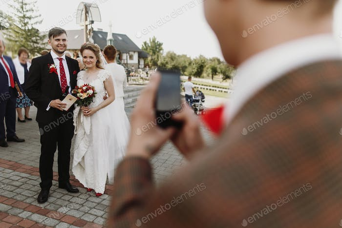man taking photo on phone of luxury happy wedding couple of newlyweds after ceremony