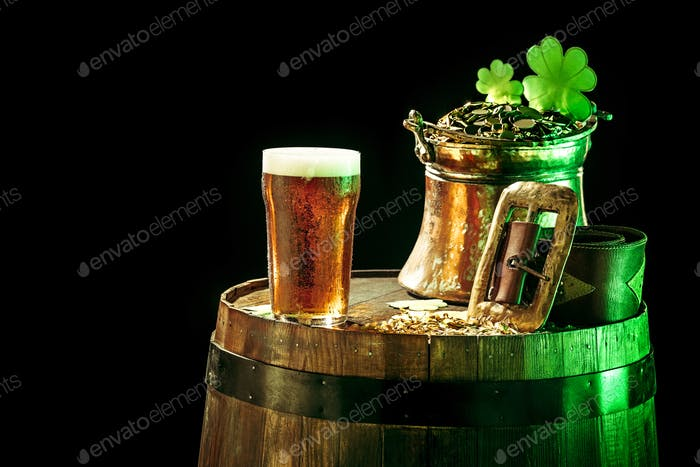 The wooden background with lots of gold coins and a large mug of beer with a green bow.