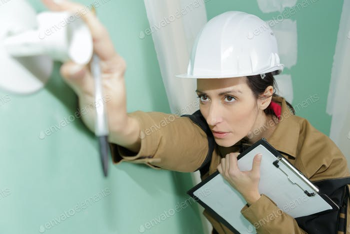 electrician supervisor is checking the installation of a wall socket