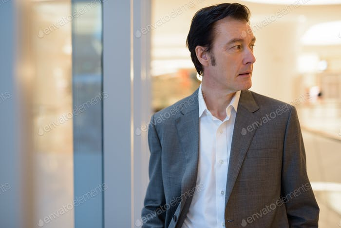 Portrait of mature handsome businessman thinking and looking away