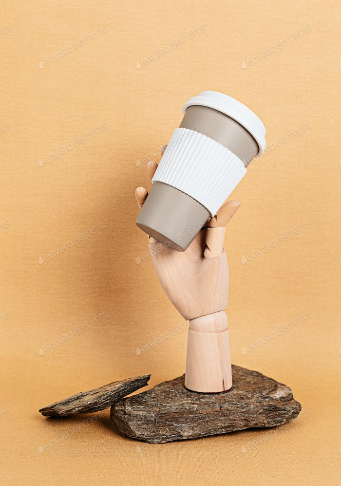 Wooden mannequin hand holding reusable coffee mug