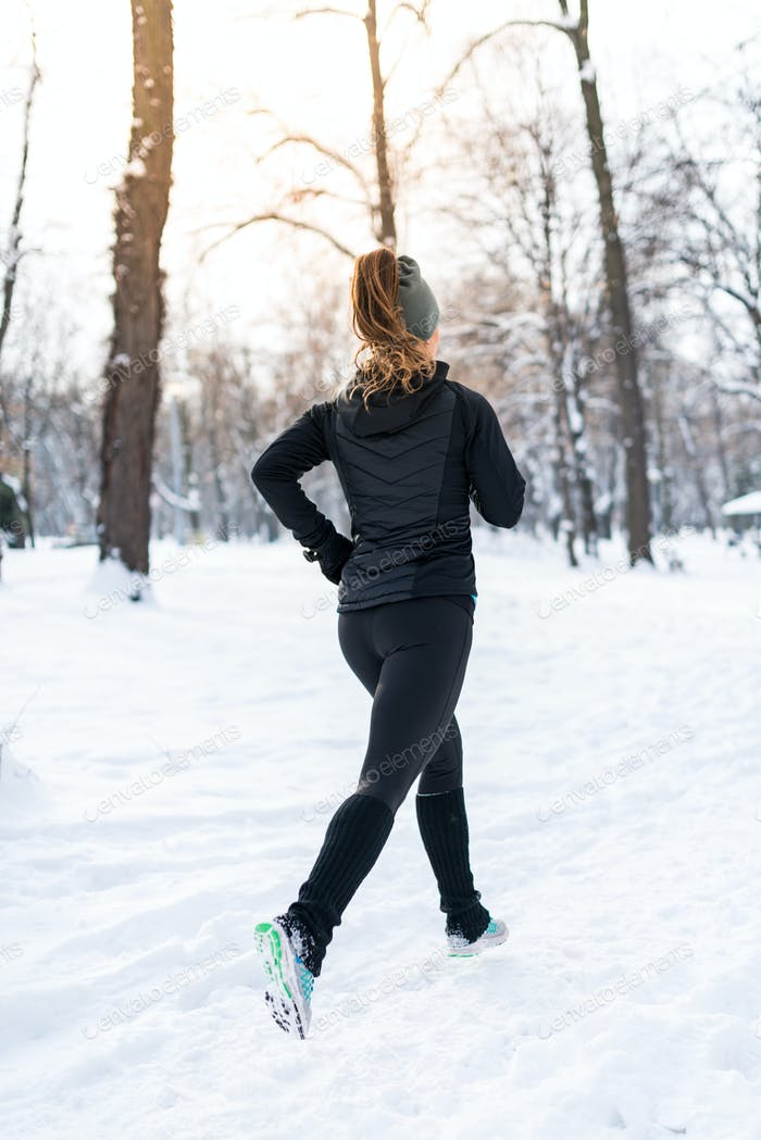 Female athlete jogging in park in winter