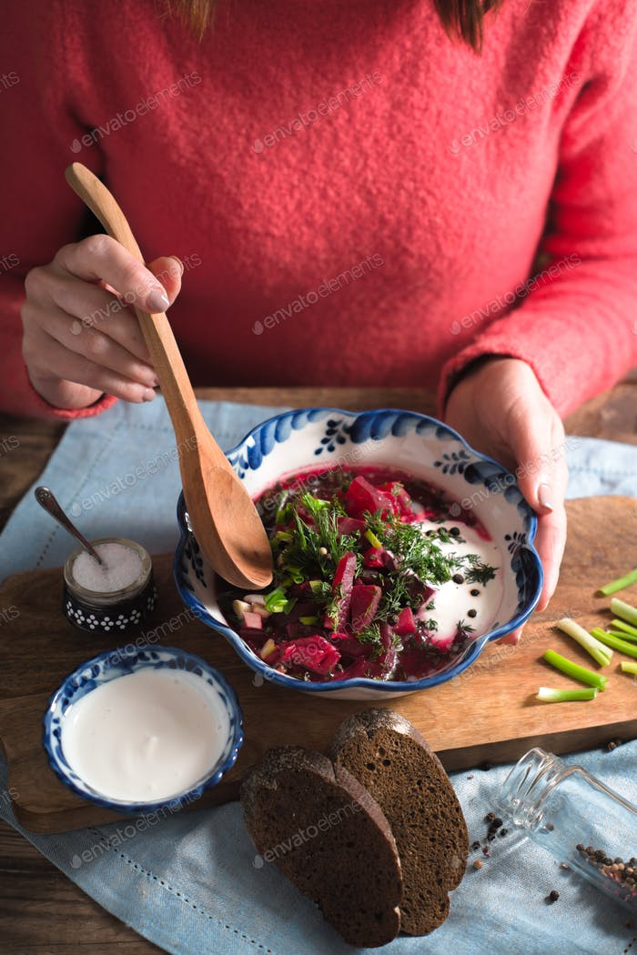 Woman eating traditional beetroot soup borsch vertical