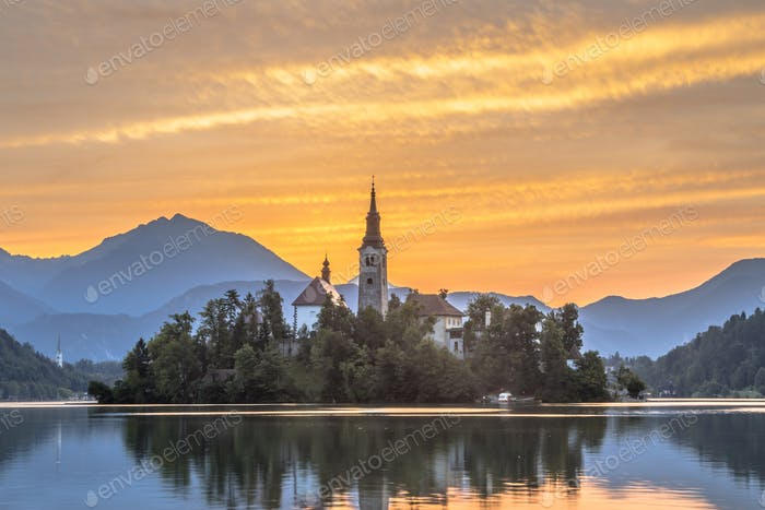 Famous Lake bled with church under orange morning sky