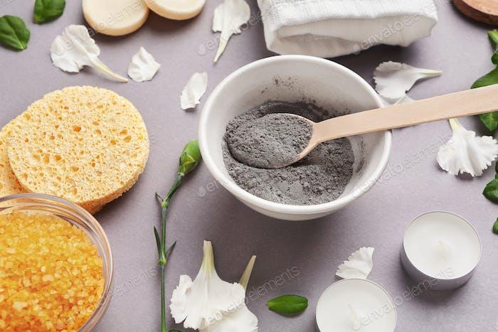 Preparing cosmetic white mud mask on gray background