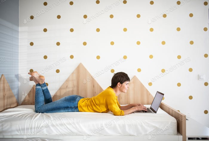 Young woman with laptop lying on bed in bedroom indoors at home.