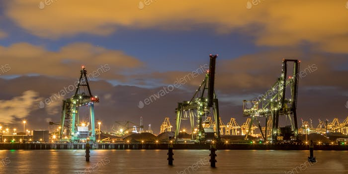 Industrial landscape with Harbor quay and loading cranes at nigh