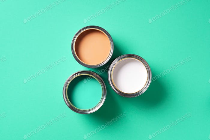 Open paint can on trendy green background. Top view, copy space. Appartment renovation, repair