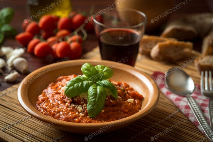 tomato soup served with ornamental basil leaf in a flat bottom crock