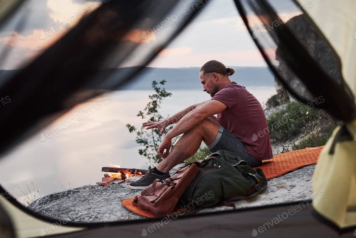 View from tent of traveller with backpack sitting on top of mountain enjoying view coast a river or
