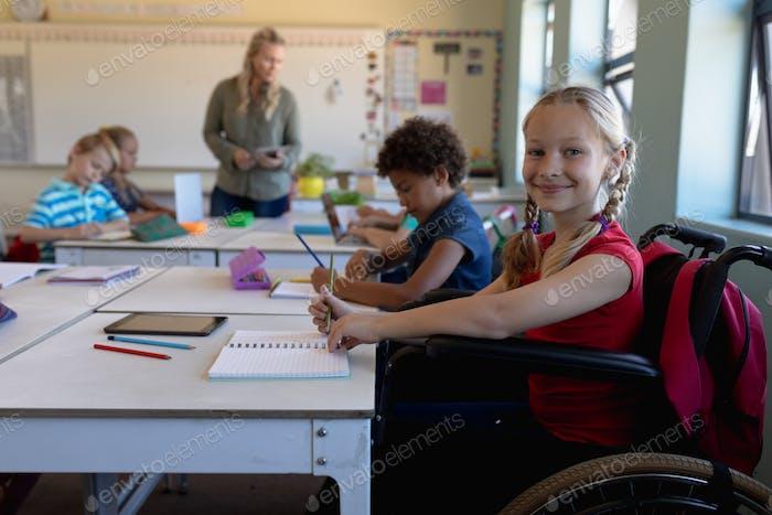 Schoolgirl sitting in a wheelchair in an elementary school classroom