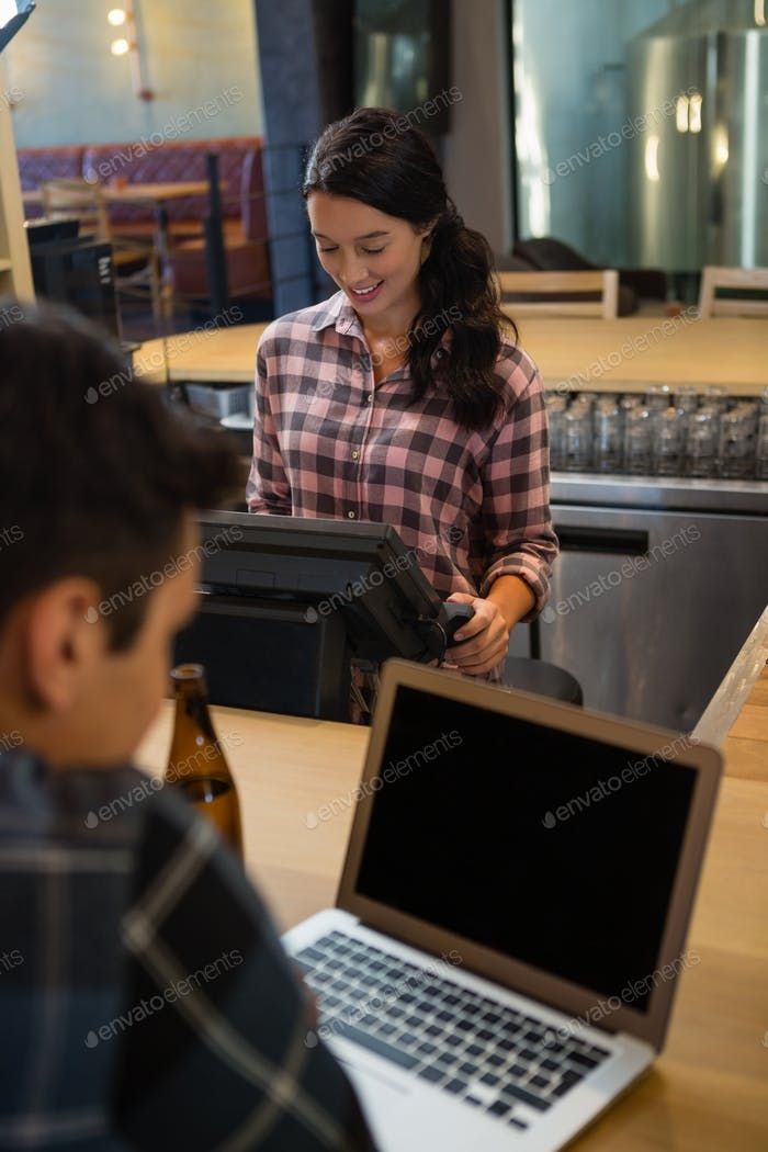 Female owner using cash register by customer at bar counter