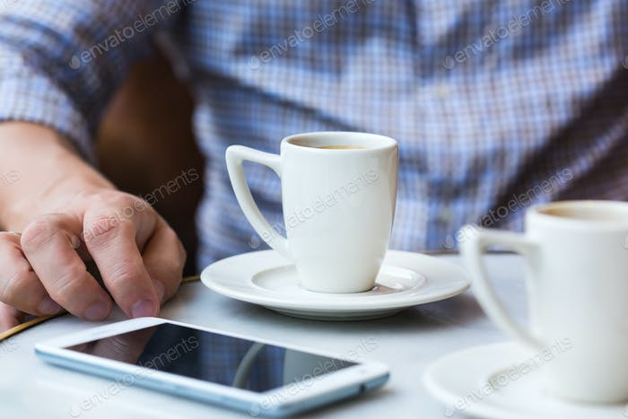 Businessman sitting in cafe, drinking morning coffee and using smartphone