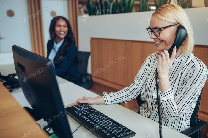 Smiling businesswoman working with a colleague at an office reception