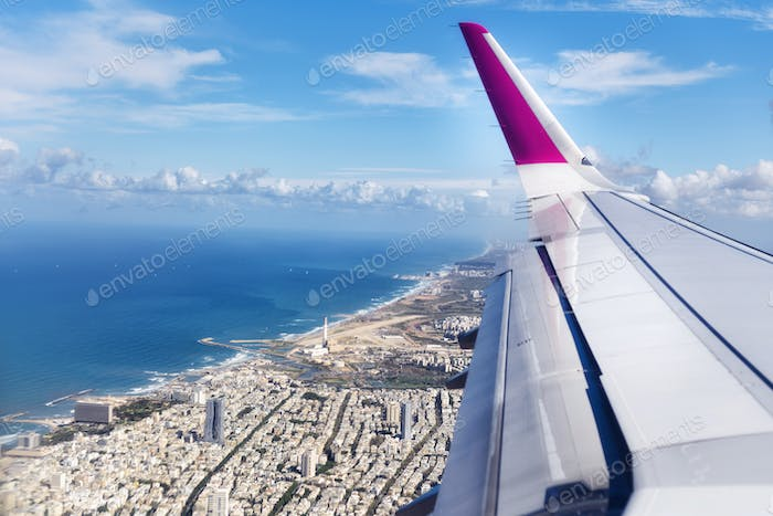 Top view from landing airplane. Window plane with copy space. Aerial view of cloud, sea, ocean and