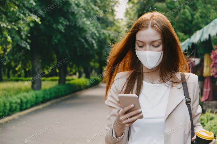 New normal, Coronavirus Covid-19 second wave. Outdoor portrait of redhead Woman with protective mask