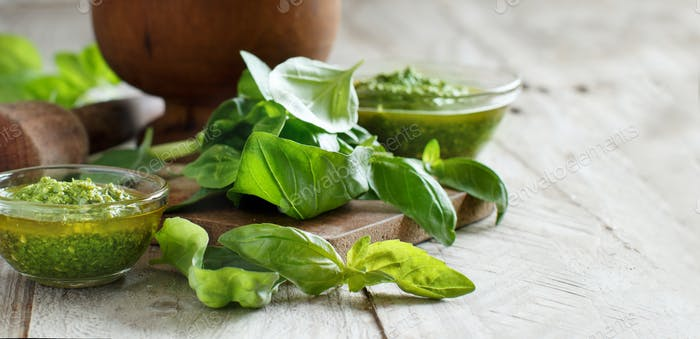 Pesto sauce and fresh basil on a wooden table