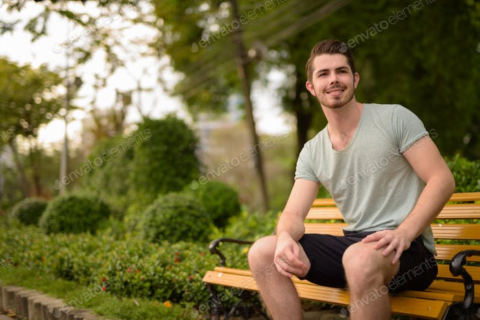 Portrait of young handsome man sitting at park while smiling