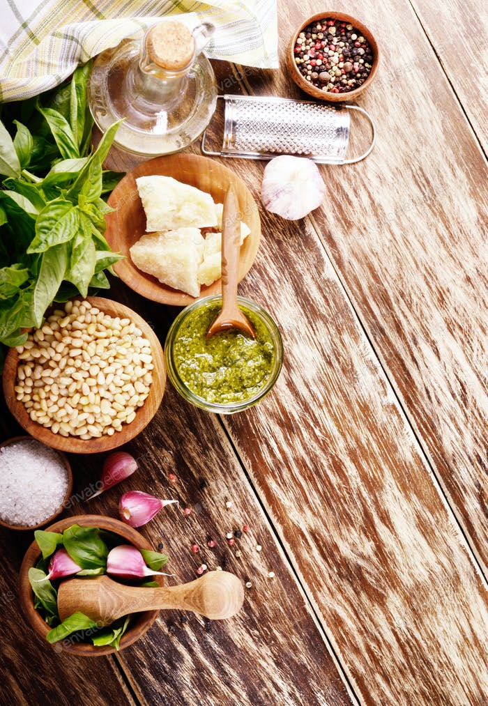 Top view of Pesto sauce ingredients and utensils on wood table w