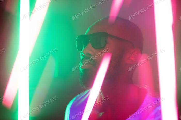 Cinematic portrait of handsome young man in neon lighted room, stylish musician