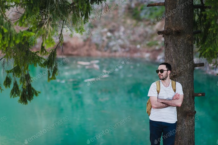 Bearded man model poses alongside a Green water Lake.