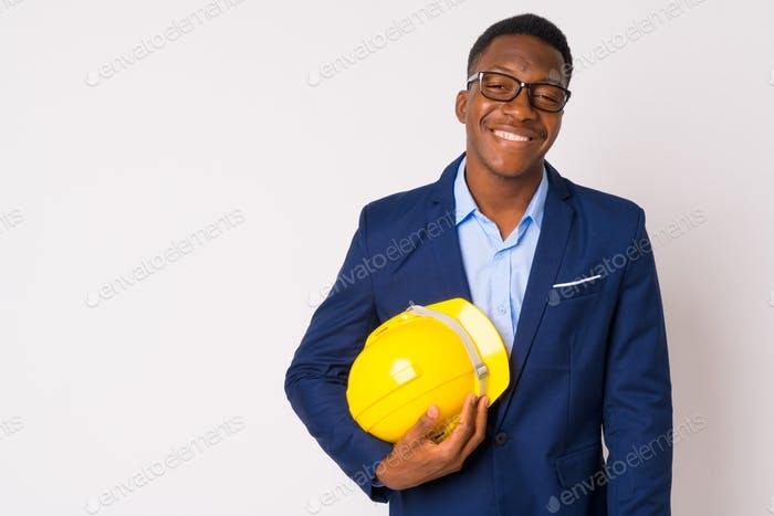 Portrait of young happy African businessman holding hardhat