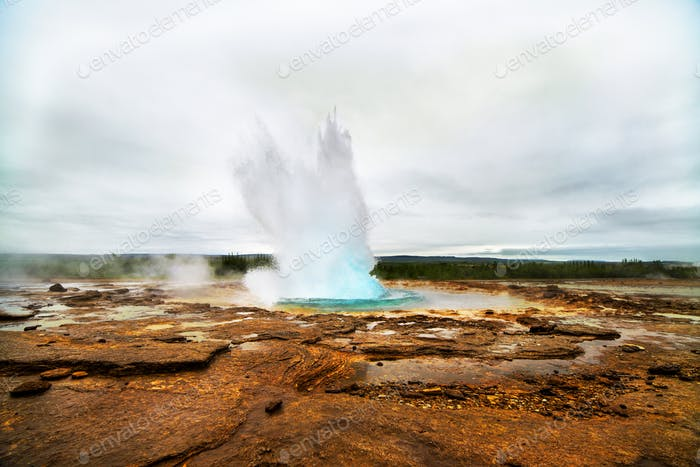 Geyser eruption in a beautifil Iceland landscape.