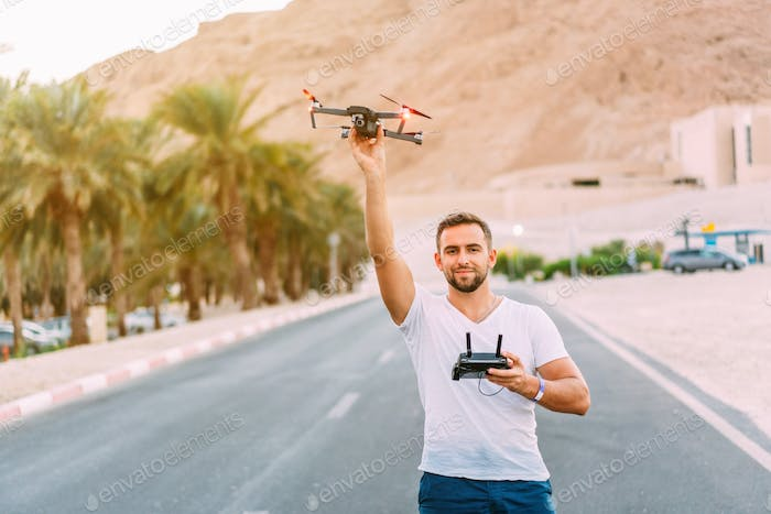 Young man holding drone before flight at nature