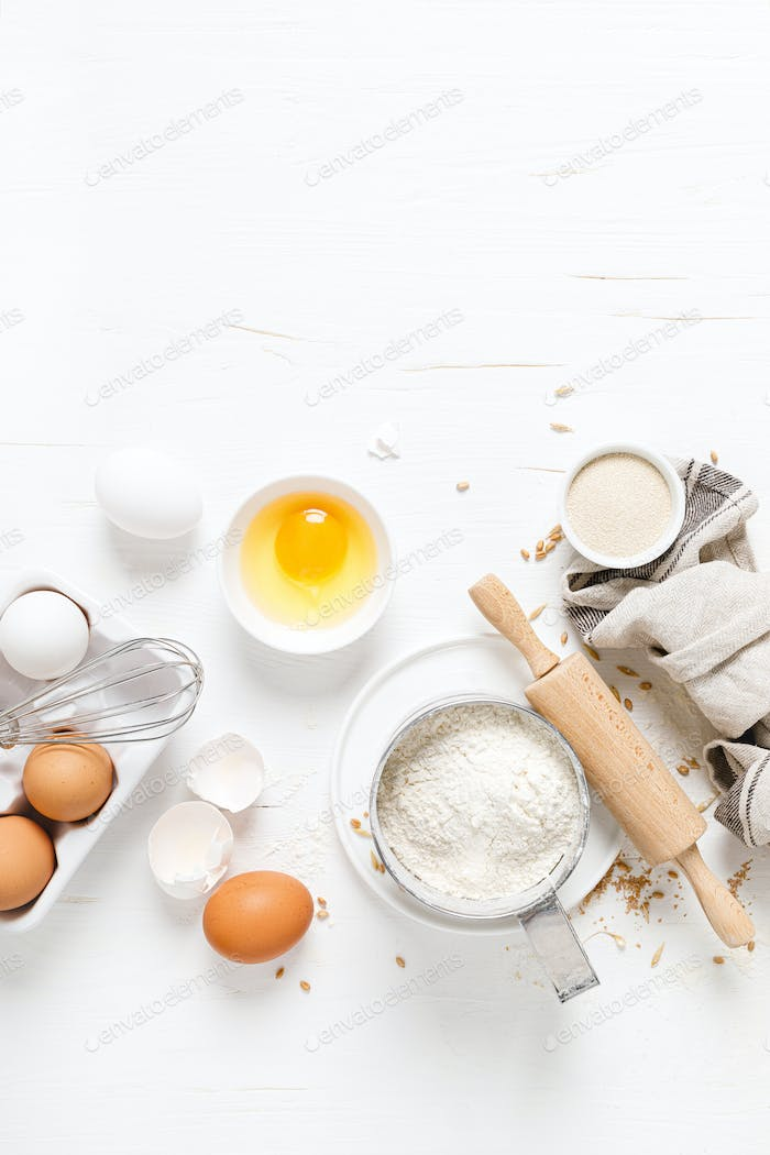 Baking homemade bread on white kitchen worktop with ingredients for cooking, culinary background