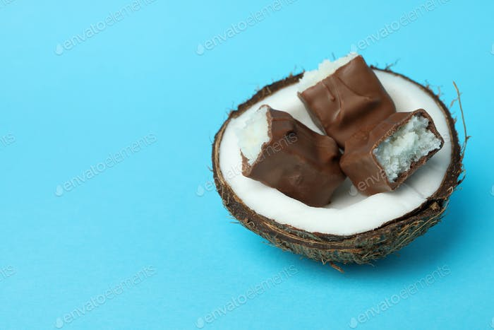 Coconut with candy bars on blue background