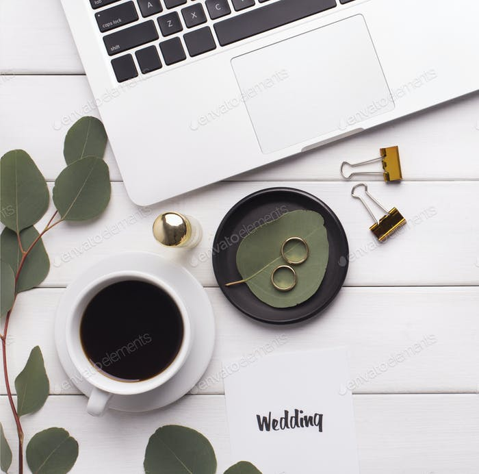 Wedding preparation on workplace with laptop and coffee