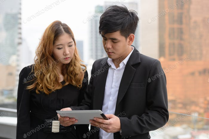 Young Asian business couple using digital tablet together in the city
