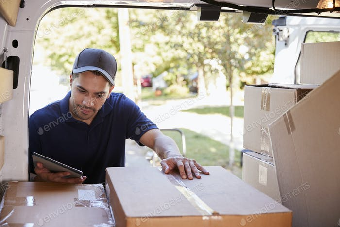 Courier With Digital Tablet Checking Packages In Van
