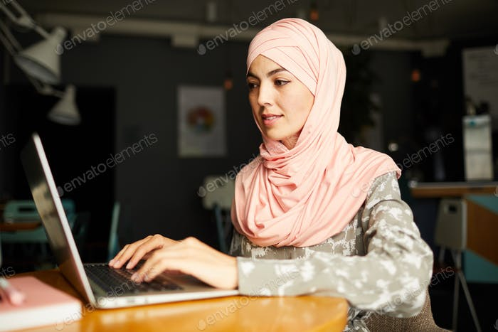 Beautiful Muslim businesswoman working at cafe table