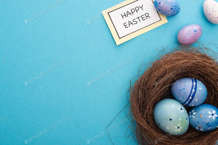 Nest With Painted Chicken And Quail Eggs With Card With Happy Easter Lettering on Blue Background