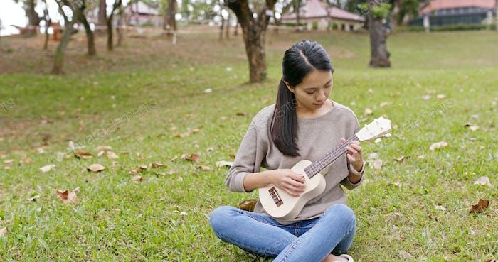 Frau spielen auf Ukulele im Park