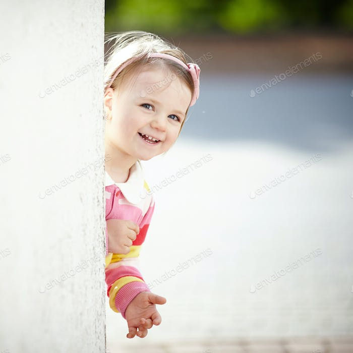 little girl peeping from behind the wall