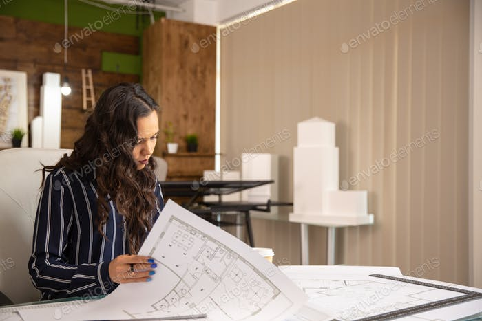 Young woman architect who controls the sketches of the real estate project