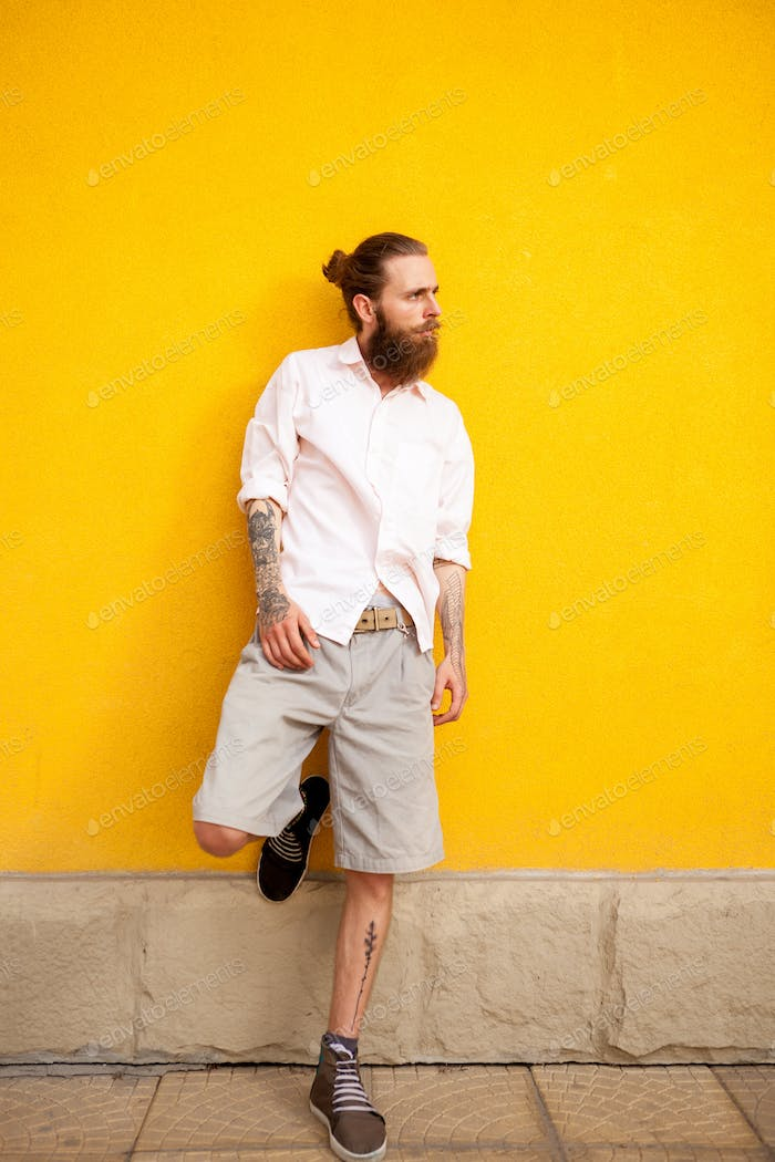 Tattooed bearded attractive man on yellow wall