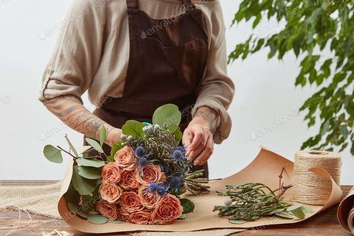 Florist at workspace. Woman's hands with tattoo are making bouquet from fresh natural flowers