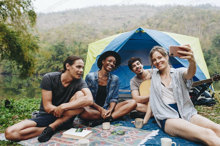 Group of young adult friends in camp site taking a group selfie outdoors