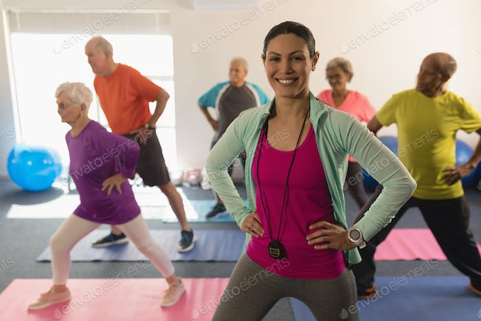 Front view of happy female trainer looking at camera while assisting senior people in fitness studio