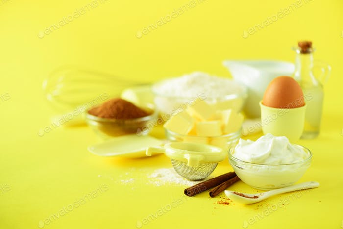 Holiday bakery background. Food frame - butter, sugar, flour, milk, eggs, oil, spoon, rolling pin