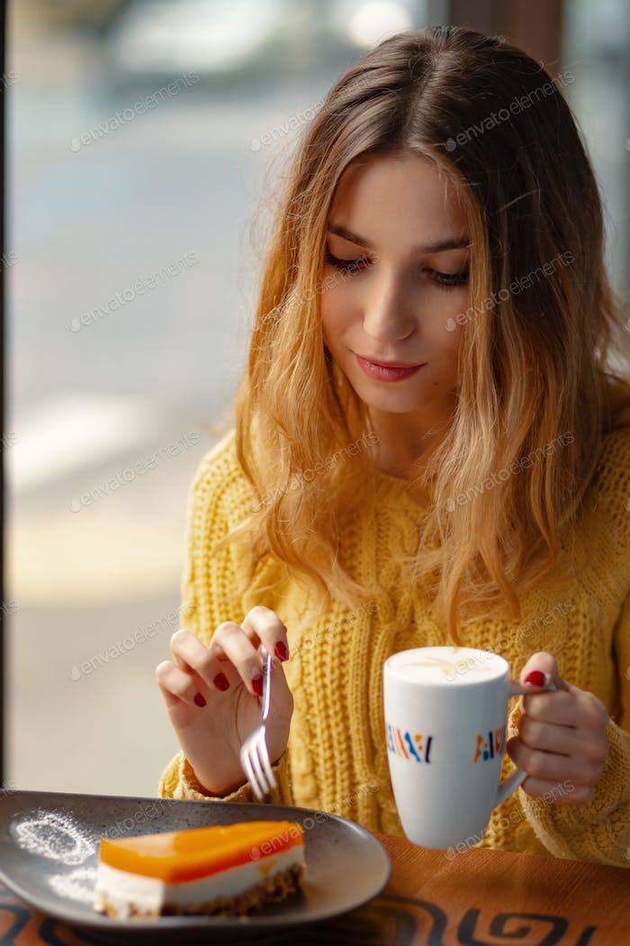 Young woman enjoying a cup of coffee and a slice of delicious ca