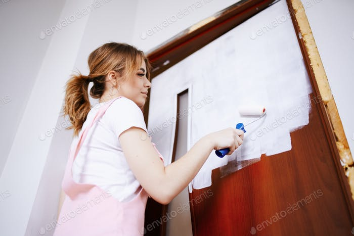 A girl in a pink work suit repaints an old door. Renovation