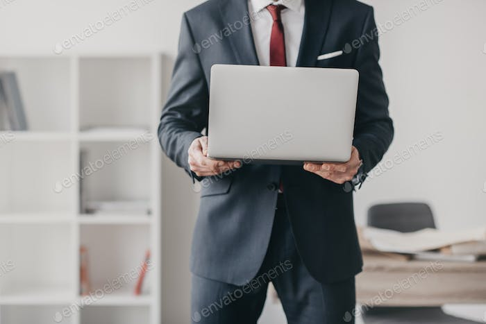 mid section view of businessman using laptop and standing in office