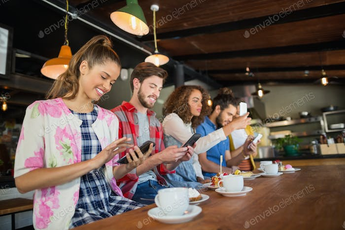 Friends using their mobile phones in restaurant