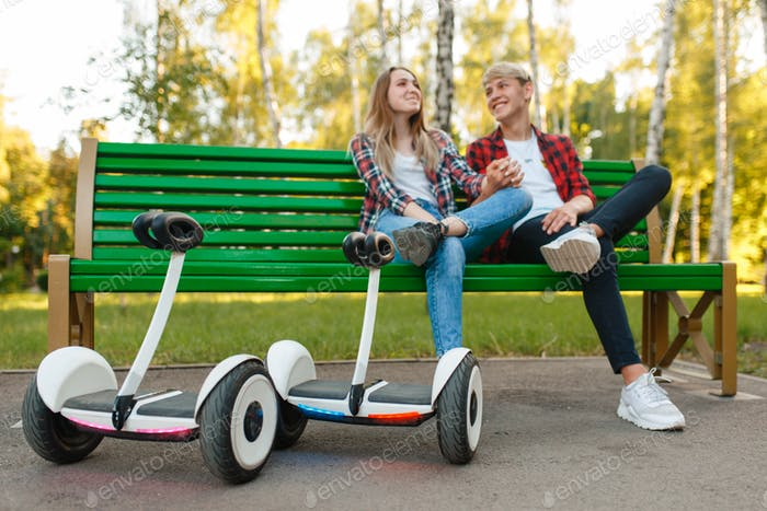 Couple with gyroboard sitting on the bench in park
