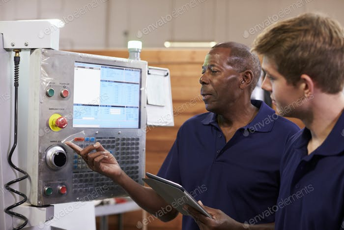 Engineer Training Male Apprentice On CNC Machine